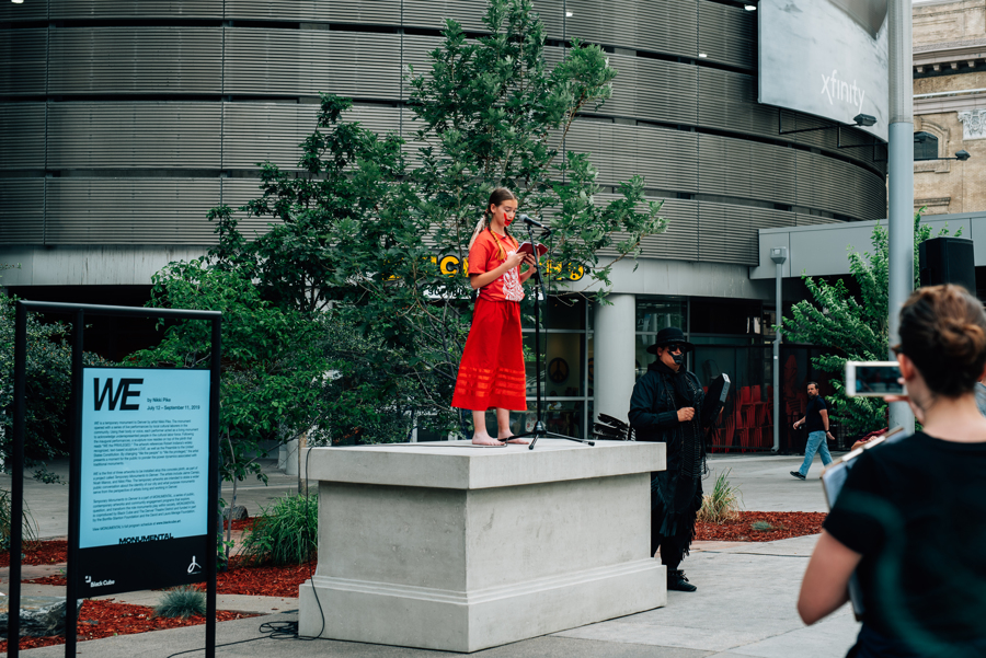 A person stands on a pedestal and speaks into a microphone.