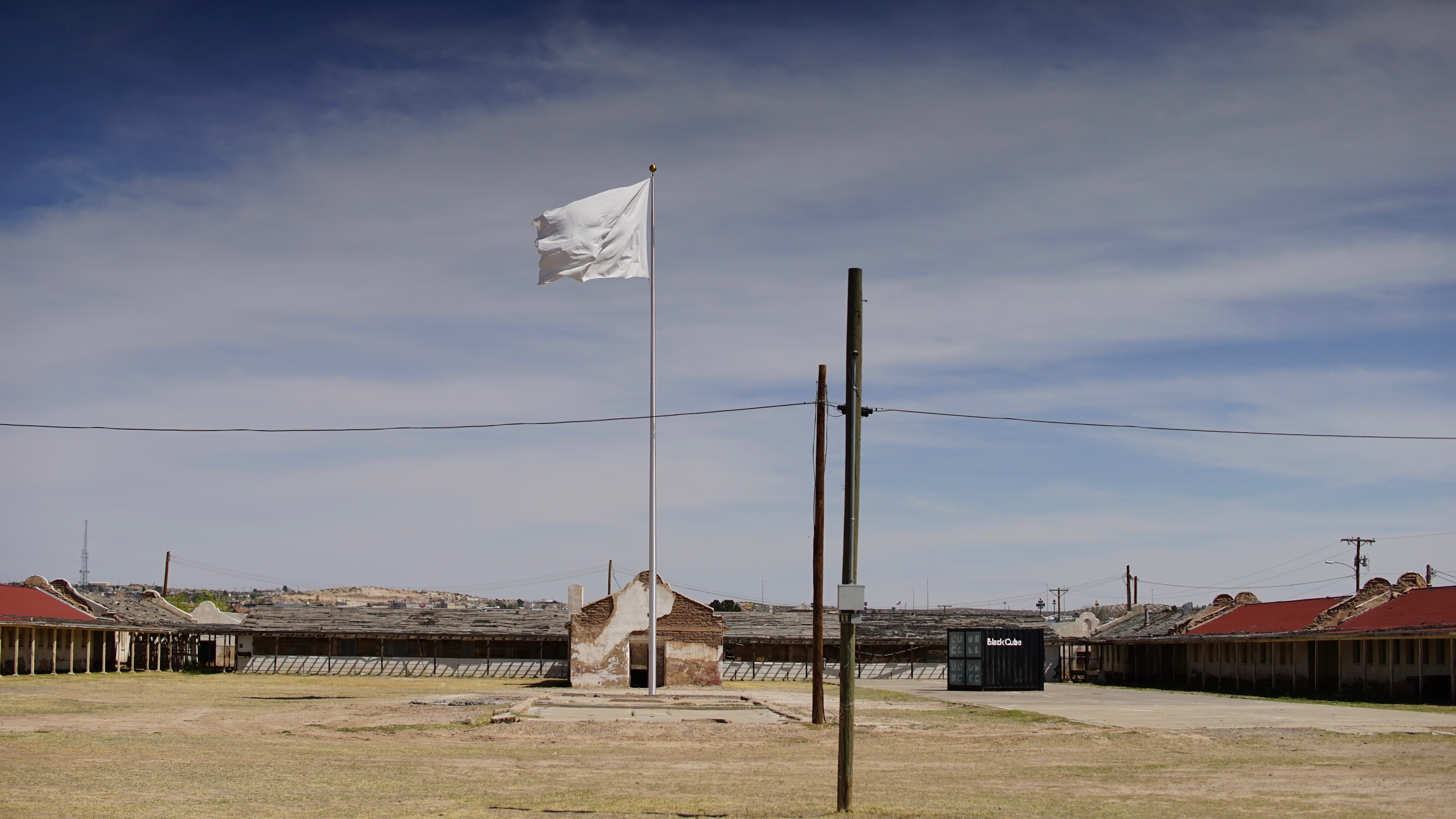 A white flag flies atop a 60-foot tall flag pole in an empty area in front of an out-of-use building